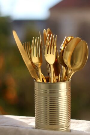 Gold colored cutlery in a can. Selective focus.