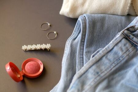 Fashionable outfit with vintage jeans, white cardigan, pink blush, beret and rings. Selective focus.