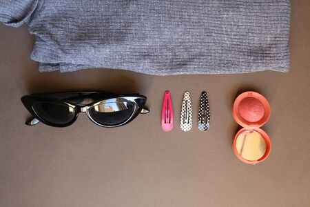 Blue turtleneck, pink blush, colorful hair clips and sunglasses on dark gray background. Top view.