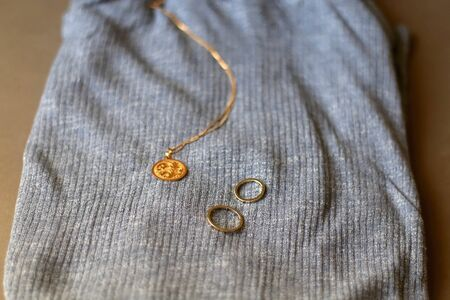 Blue turtleneck, gold necklace with pendant and rings. Selective focus.