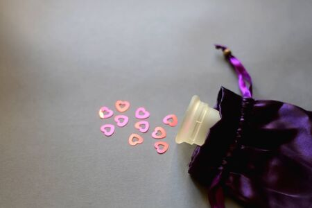 Menstrual cup in purple pouch and red heart sequins symbolizing menstrual cycle. Selective focus. Stock fotó