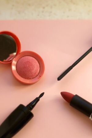 Make-up products on pale pinkbackground: pink blush, mascara, eyeliner and lipstick. Selective focus.