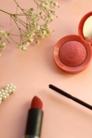Blush, mascara, lipstick, beret and gypsophila flowers on pale pink background. Selective focus. Stock fotó