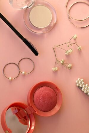 Beauty products and fashionable accessories on pale pink background: blush, mascara, eyeliner, lipstick,k rings, hoop earrings, beret and gypsophila flowers. Top view.