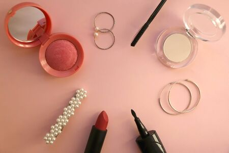 Beauty products and fashionable accessories on pale pink background: blush, mascara, eyeliner, highlighter, lipstick, beret, rings and hoop earrings. Top view. 写真素材