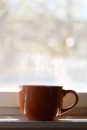 Cup of tea on a rustic window. Selective focus.