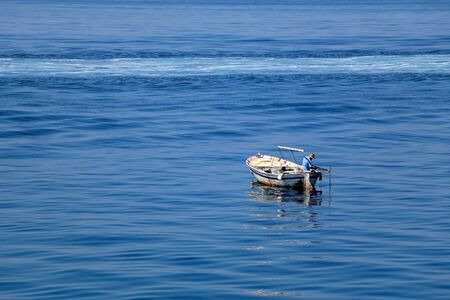 Unrecognizable fisherman on a small rustic fishing boat in Croatia.