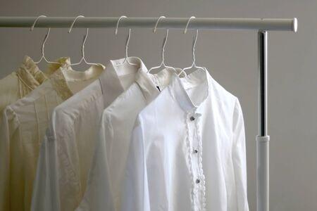 Colección de camisas y blusas blancas en un perchero. Enfoque selectivo.