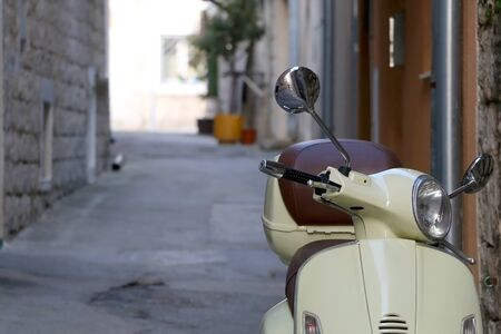 Pastel yellow scooter parked in a traditional narrow alley in Split, Croatia. Selective focus. Foto de archivo