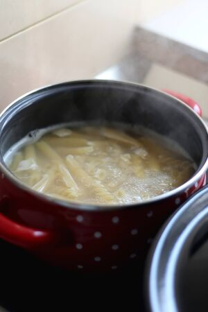 Cooking pasta in boiling water. Selective focus. Stock Photo