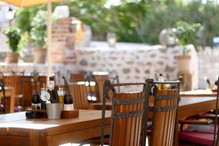 Wooden furniturein a garden of Mediterranean restaurant. Selective focus.