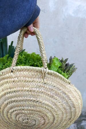 Unrecognizable person holding straw bag with fresh leek, lettuce and asparagus. Selective focus. Stock Photo