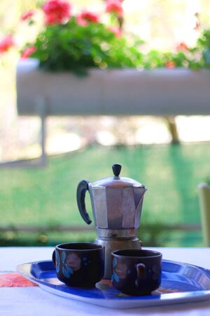 Vintage coffee pot and two cups in a garden. Selective focus.