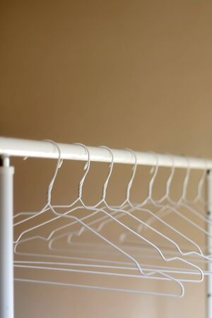 White empty hangers on a clothing rack. Selective focus.