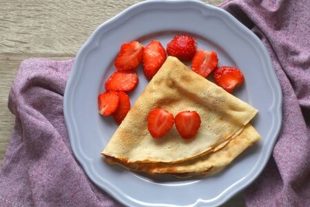 Homemade crepe with marmalade and sliced strawberries. Top view.