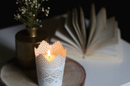 Candle holder with lit candle, golden vase with gypsophila flowers and open book on a table. Selective focus, moody lighting. Reklamní fotografie