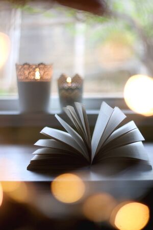 Open book and two lit candles on a table. Bokeh string lights in the foreground. Selective focus. Stock Photo