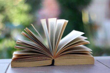 Open book in a garden. Selective focus.