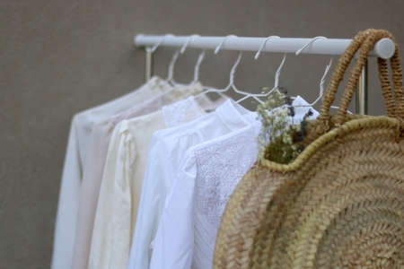 Clothing rack with white and neutral garments and wicker bag with flowers. Selective focus, gray concrete background.