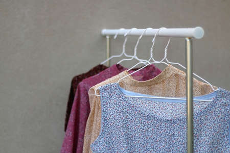 Colorful floral pattern garments on a clothing rack. Selective focus.