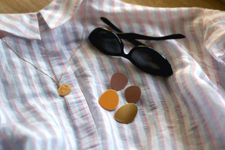 Striped pastel blouse, sunglasses, gold earrings and necklace. Selective focus.