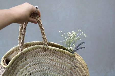 Unrecognizable person holding wicker bag with flowers. Selective focus.