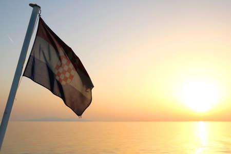 Flag of Croatia on a boat, illuminated by beautiful sunset light. Selective focus.