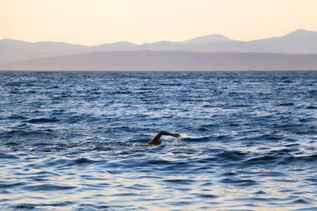 Unrecognizable person swimming at sunset. Beach in Sutivan, island Brac, Croatia. Selective focus. Zdjęcie Seryjne