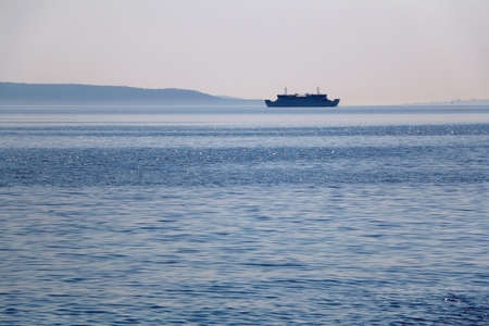 Sunlight reflecting in the sea, ferry boat in the background. Selective focus.