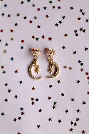 Fashionable gold earrings on pale pink background with colorful star shaped confetti. Top view.