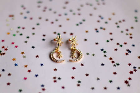 Fashionable gold earrings on pale pink background with colorful star shaped confetti. Selective focus. Zdjęcie Seryjne