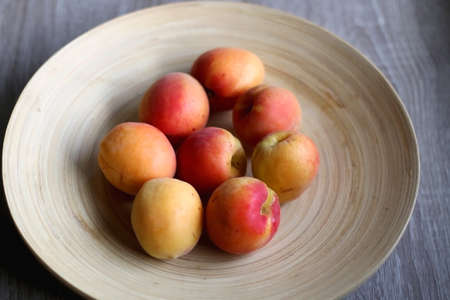 Wooden bowl with fresh organic apricots on the table. Selective focus.