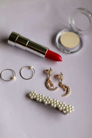 Lipstick, eyeshadow, gold rings, earrings and pearl barrette on pale lilac background. Selective focus.