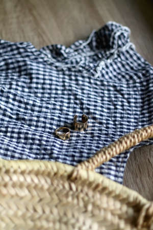 Gingham top, straw bag and gold rings. Selective focus.
