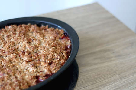 Homemade peach crumble served on a table. Selective focus.
