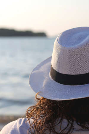 Unrecognizable person wearing a white straw hat on a beach. Selective focus.