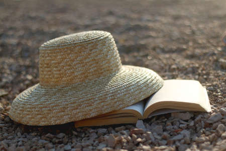 Straw hat and open book on a beach at sunset. Selective focus.