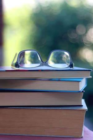 Stack of books and reading glasses outdoor. Selective focus.