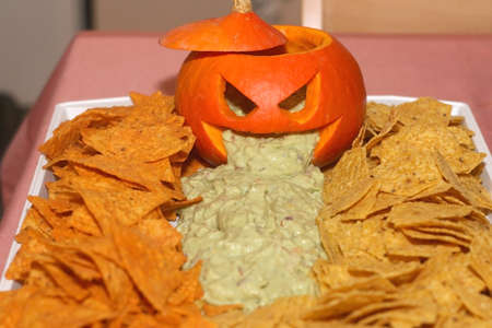 Carved pumpokin filled with guacamole and tortilla chips. Halloween party food. Selective focus.