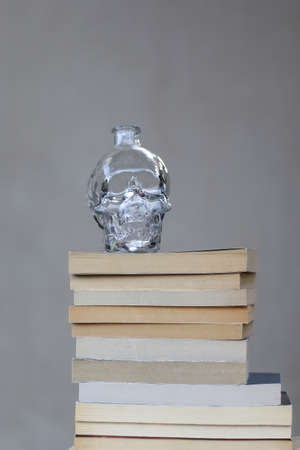 Stack of paperback books and skull shaped decoration. Selective focus.
