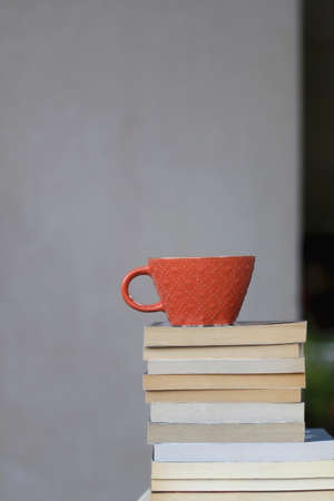 Stack of paperback books and a cup of coffee or tea. Selective focus. 版權商用圖片