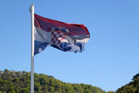Flag of Croatia blowing in the wind. Forest in the background. Selective focus.