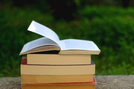 Stack of books in the garden. Selective focus.