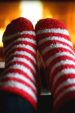 Feet in fuzzy festive socks, resting by the fireplace. Selective focus.