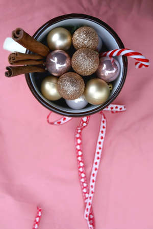 Enamel bag with festive bow, filled with Christmas baubles, cinnamon sticks and candy cane. Pink background, flat lay.
