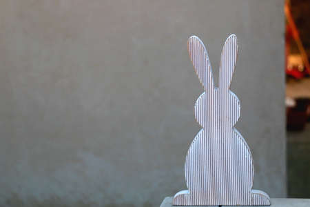 Wooden bunny and concrete wall, minimal Easter decoration. Selective focus, copy space.