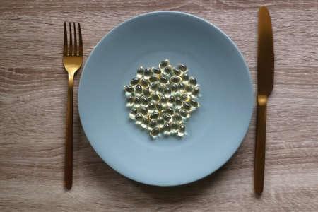 Vitamin D pills on a plate. Flat lay.
