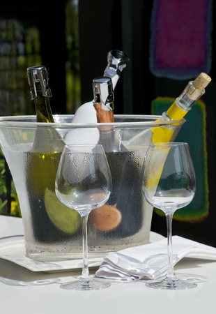 Served white wine with two empty glasses on a sunny bar table photo