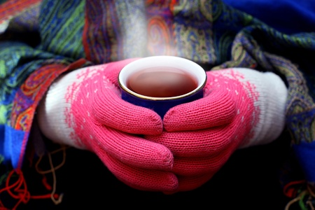 Two hands in woolen gloves holding hot cup of tea photo