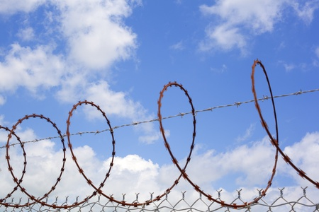Barbed wire against sunny sky and clouds photo